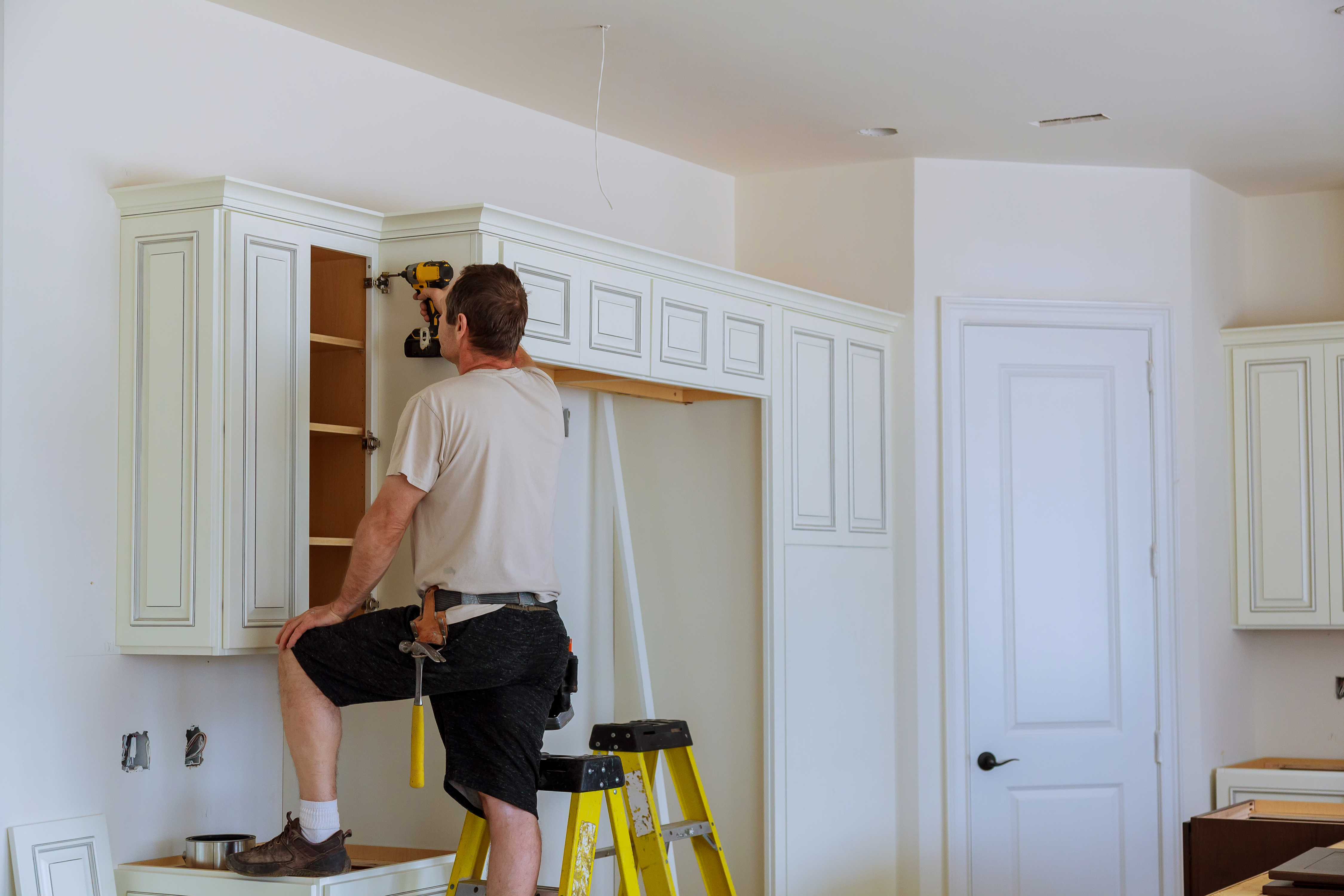 Worker Installs Doors To Kitchen Cabinet Installation Of On Cabinets