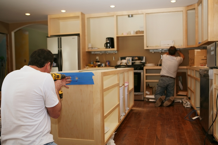 Cabinet Maker Installing Custom Made Maple Cabinets To Kitchen Island While Electrician Installs Under